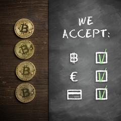 """Bitcoin Münzen auf Holzuntergrund mit Wandtafel und Hinweis """"We accept:"""" und den drei Optionen Bitcoin, Cash und Karte"""