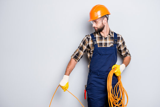 Half face portrait of busy stylish electrician with stubble in overall, shirt, hardhat installing, laying a cable, having rolled wire in hand, standing over grey background