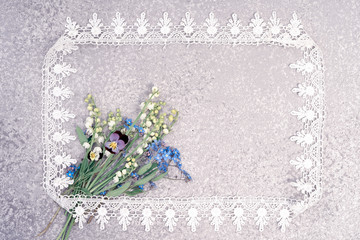 lily of the valley, pansies and forget me not bouquet laying on an silver background in the lace frame with copy space for your greeting or invitation text. Holiday card.