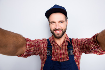 Self portrait of joyful cheerful mechanic with stubble in blue overall, shirt shooting selfie on front camera with two hands, isolated on grey background