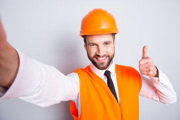 Self portrait of handsome attractive joyful man with stubble in shirt, tie and hard hat, showing like, thumb up, yes, done sign with finger, isolated on grey background, having leisure, fun