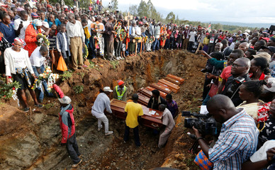 Relatives arrange the coffins of their kin inside a mass grave during the burial of people killed when a dam burst its walls, overrunning nearby homes, in Solai town near Nakuru