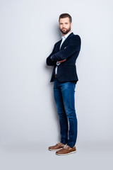 Full size body portrait of elegant trendy teacher with stubble having his arms crossed looking at camera isolated on grey background, wearing jacket, jeans, shirt