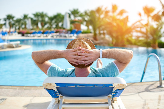 Relax in the pool summer. Young and successful man lying on a sun lounger at the hotel on the background of sunset, concept time to travel