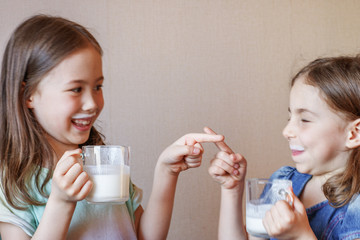 two funny little girls with white mustache from milk