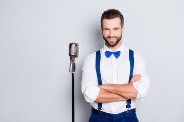 Portrait of famous joyful singer with bristle, wearing blue pants bowtie suspenders shirt, having his arms crossed, standing near mic isolated on grey background