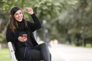 Ragazza mora vestita di nero e seduta in una panchina ascolta felice la musica dalle sue cuffie e il suo cellulare.