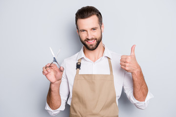 Portrait of cheerful positive barber with stubble in shirt having scissors in hand showing thumb up approve sign with finger, looking at camera, isolated on grey background