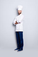 Full size body portrait of joyful positive chef cook with stubble in beret, having his arms crossed, isolated over grey background, looking at camera