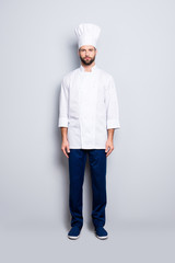 Full size fullbody portrait of attractive stylish chef cook with stubble in beret, looking at camera, isolated over grey background