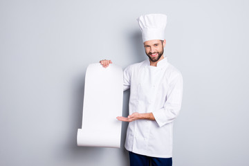 Portrait with empty place of cheerful positive chef cook in beret showing with palm clean open paper roll with empty place for product, isolated on grey background