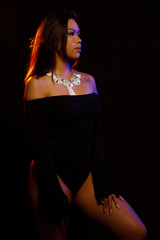 Fit young asian woman in black one piece and necklace poses against black under orange and blue colored lights