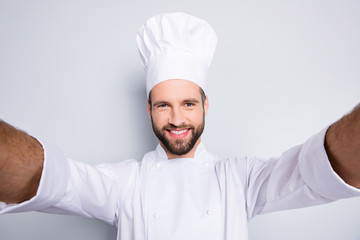 Self portrait of cheerful attractive chef cook in beret and white outfit with stubble shooting selfie on front camera of smart phone with two hands, isolated on grey background
