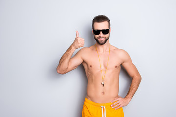 Portrait of fit sportive lifeguard with stubble in yellow shorts holding hand on waist showing thumb up sign isolated on grey background