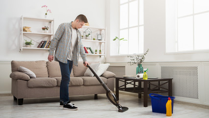 Young man cleaning house with vacuum cleaner