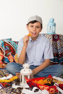 Happy young Muslim boy fasting Ramadan , eating Ramadan fruits : dates, apricots, figs; and palms, ready for iftar (brakfast ) in Ramadan