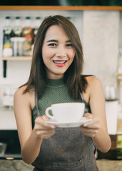Young woman bartender holding coffee cup in coffee shop