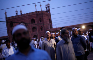 Muslim men look towards the sky to spot the crescent moon, on the eve of the holy fasting month of Ramadan, at the Jama Masjid (Grand Mosque) in the old quarters of Delhi