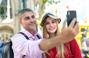 Happy couple making selfies during city visit. Tourism and holiday concept