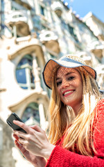 Happy beautiful blonde girl using smartphone visiting city. Tourism and holiday concept