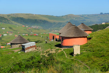 Rondawels, traditional thatched-roofed huts scattered through the grassy hills in a village near Coffee Bay on the Wild Coast in Eastern Cape, South Africa Fototapete