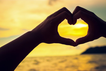 Beautiful silhouette of hand shape of love heart with sunset and beach background.
