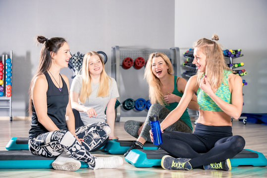 happy laughing women after training in the gym talking and resting