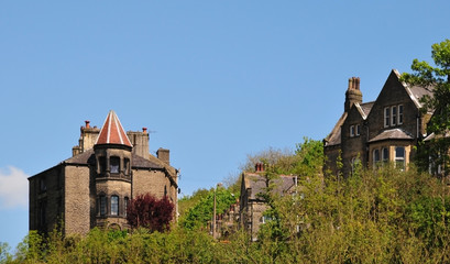 tall stone gothic houses set in the woodland landscape i hebden bridge west yorkshire with blue sky