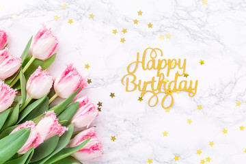 Pink tulips and gold Happy birthday letters with festive sprinkles on white marble background. Spring and celebration concept. Copy space