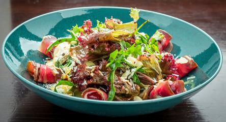 Fresh prosciutto ham and vegetables salad closeup