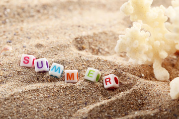 Inscription Summer by cubes with coral on beach sand