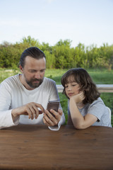 father and son watching the smartphone garden on the terrace on a summer day, family