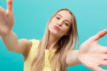 Close-up portrait of attractive young woman stretching her arms, wants to hug and kiss you. Isolated on blue background.