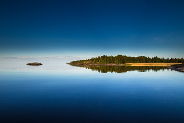 Reflection of the island in the water. Karelia. Wild nature of Finland.