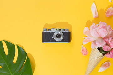 Top view of summer background with Tropical palm tree leaf, vintage photo camera, flowers on a trendy bright yellow background, flat lay