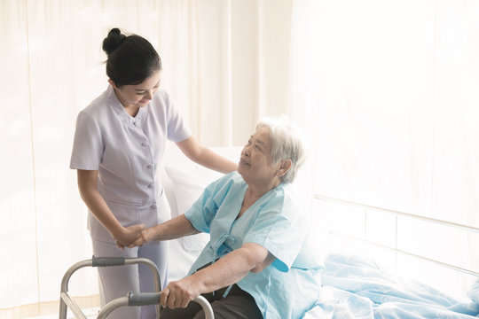 Nurse with patient. Routine health check and assisting elderly patient to walk. Female nurse with senior chinese woman.