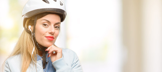 Young woman with bike helmet and earphones thinking and looking up expressing doubt and wonder