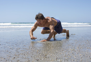 Man doing beach bear crawl workout