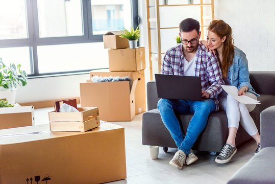 Young couple moving in new home. Sitting and relaxing after unpacking. Searching home decorating ideas on laptop.