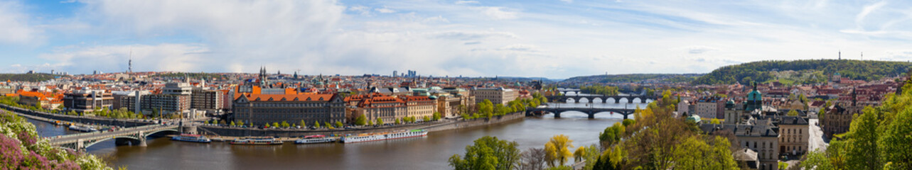 PRAGUE, CZECH REPUBLIC - APRIL, 30, 2017: Spring city ultra wide panoramic view from Letenske garedn. Old and modern buildings and bridges over Vltava river.