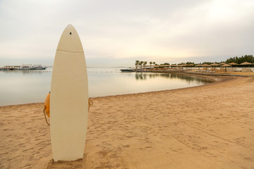 White surf board pinned in sandy beach in front of sea bay on cloudy day