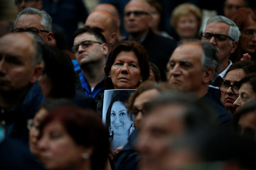 A woman holds a picture of assassinated anti-corruption journalist Daphne Caruana Galizia during a vigil and demonstration marking seven months since her murder in a car bomb, at her makeshift memorial outside the Courts of Justice in Valletta