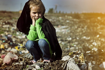 A homeless child sits on the mud amidst a garbage dump and thinks about life