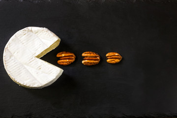 Camembert cheese on the cutboard with pecan nuts