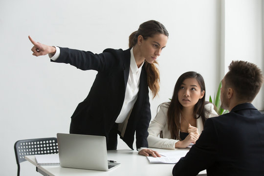 Angry mad female HR representative pointing at door, asking male job candidate to leave, making verbal sign. Applicant show no respect, ignoring requests. Dismissal, bad interview, annoyed employers.