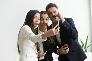 Coworkers trying mustache accessory, making silly faces posing to camera while making selfie on smartphone. Colleagues having fun at work, playing childish and taking pictures during work break.