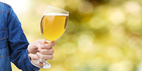hand with beer glass and abstract background