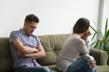Sad offended woman looking far away in window not talking to husband, thinking about relationships ending, man with arms crossed being upset about misunderstanding and possible break up.