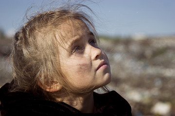 A beggar girl in a garbage dump looks with sadness into the sky