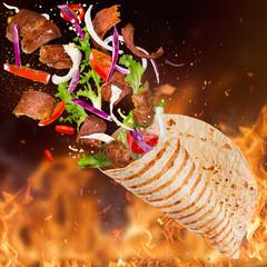 Turkish Kebab yufka with flying ingredients and flames.